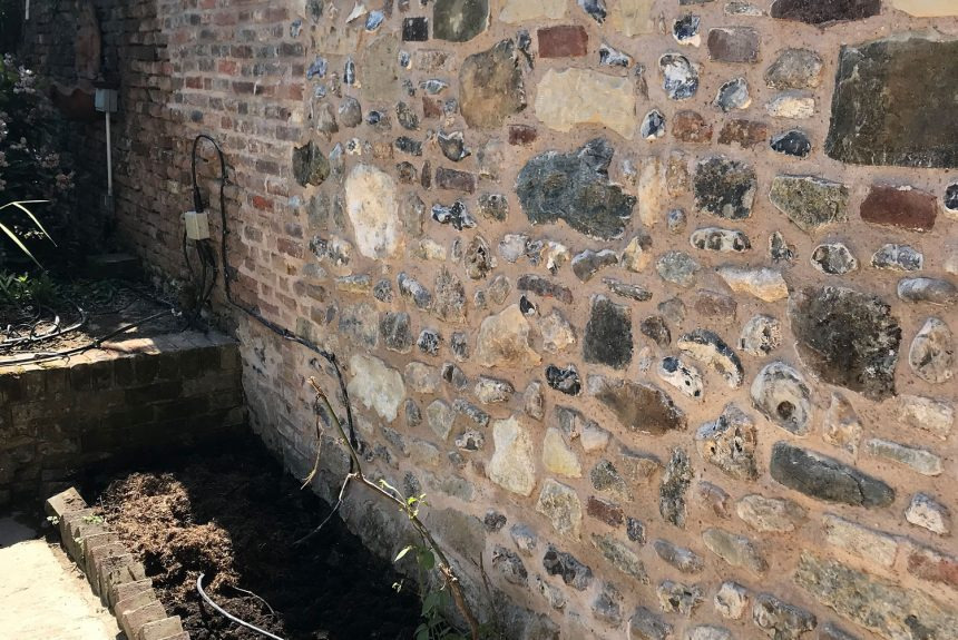 The completed flint stone wall in Chichester blending into the old part of the wall